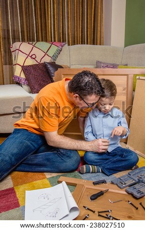 Portrait of father and son assembling with tools a new furniture for home. Family leisure concept