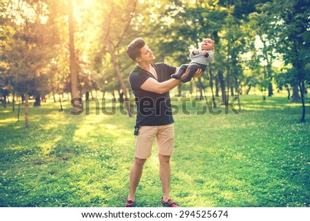 Portrait of father and son having fun in park, father holding baby, infant. Concept of family day in the park with young parents  - stock photo