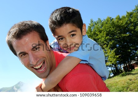 Portrait of father and son having fun in the mountain - stock photo