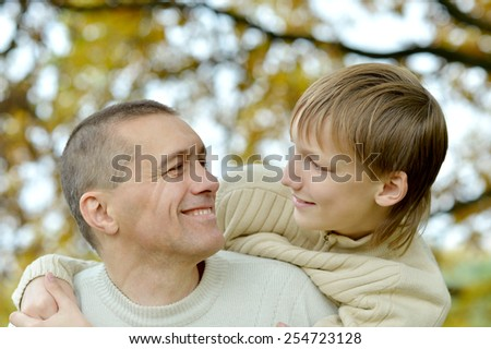 Portrait of father and son in autumn park - stock photo