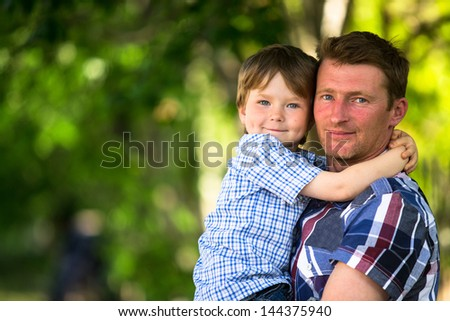 Portrait of father and son in the park - stock photo