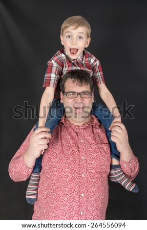 portrait of father and son on a black background - stock photo