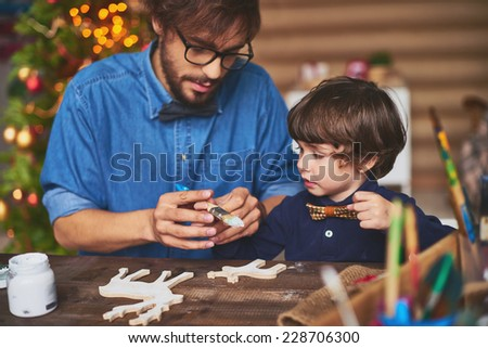 Portrait of father and son painting wooden deer shapes - stock photo