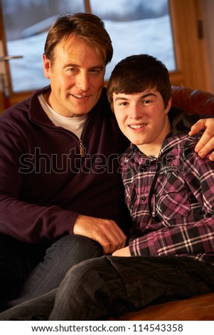 Portrait Of Father And Son Relaxing On Sofa Together