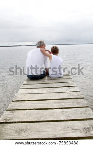 Portrait of father and son sitting on a pontoon - stock photo