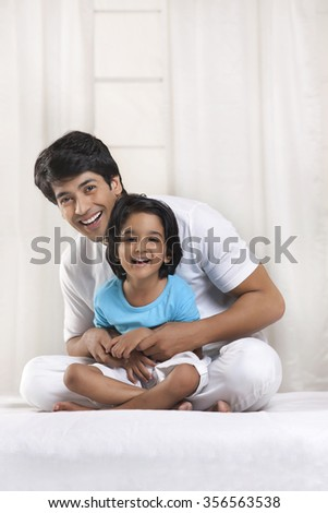 Portrait of father and son smiling - stock photo