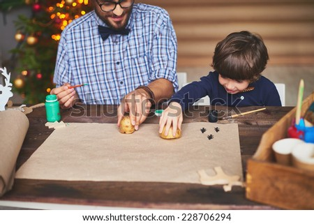 Portrait of father and son stamping Christmas prints on paper - stock photo