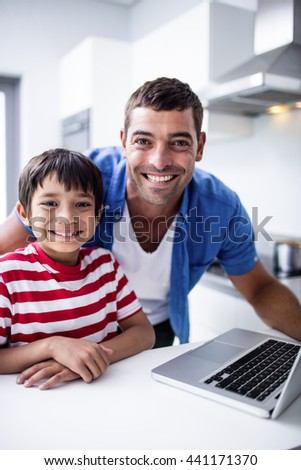 Portrait of father and son using laptop in kitchen at home - stock photo