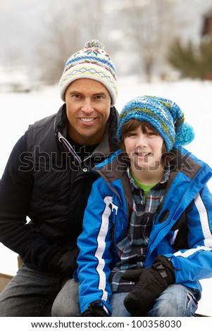 Portrait Of Father And Son Wearing Winter Clothes In Snowy Landscape - stock photo
