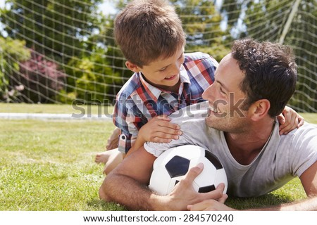 Portrait Of Father And Son With Football - stock photo