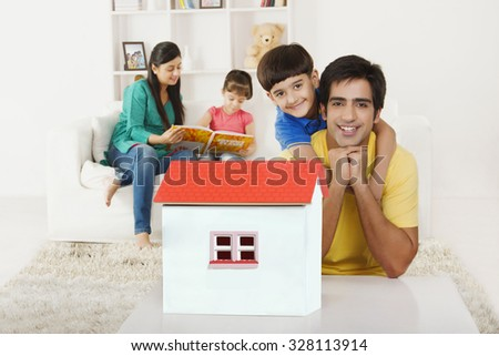 Portrait of father and son with house - stock photo