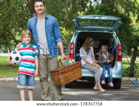 Portrait of father and son with picnic basket while mother and daughter sitting in car trunk - stock photo