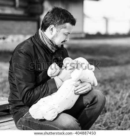 Portrait of father feeding newborn baby - stock photo