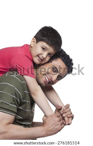 Portrait of father giving piggyback ride to son over white background