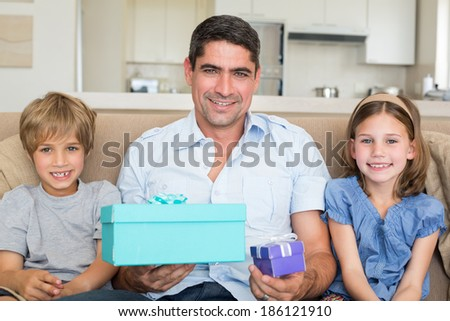 Portrait of father holding gift boxes while sitting with children on sofa at home - stock photo
