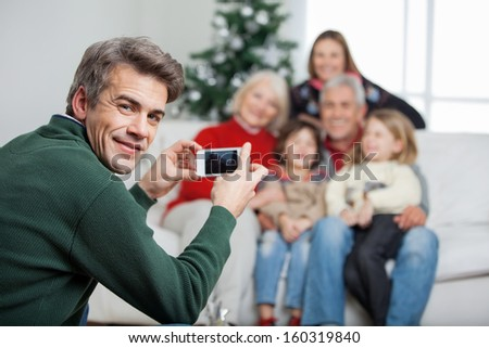 Portrait of father photographing family through mobilephone during Christmas at home - stock photo
