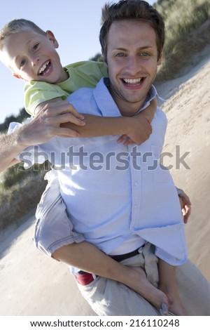 Portrait of father piggybacking son on beach - stock photo