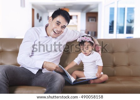 Portrait of father spending time with his daughter while reading book on the brown couch in the living room