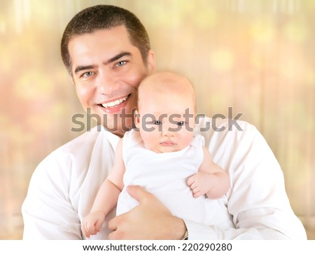 Portrait of father with baby at home, cheerful young daddy holding newborn child on hands over blur bokeh background, happy family concept - stock photo