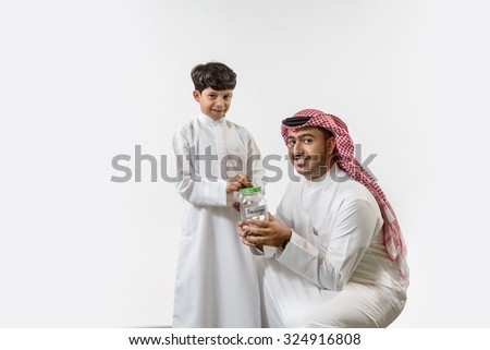 Portrait of father with son inserting money in money box - stock photo
