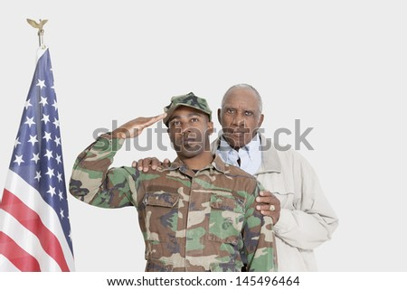 Portrait of father with US Marine Corps soldier saluting American flag over gray background - stock photo