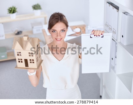 Portrait of female architect holding a little house, standing in office . - stock photo