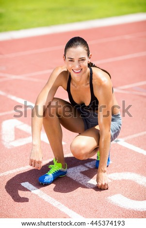Portrait of female athlete kneeling on running track on a sunny day