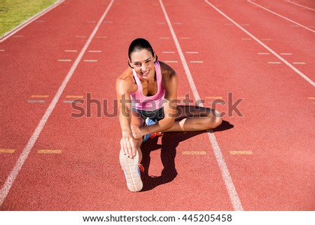 Portrait of female athlete stretching her hamstring on running track