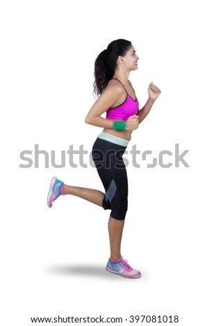 Portrait of female athlete wearing sportswear and doing workout by running in the studio, isolated on white background - stock photo
