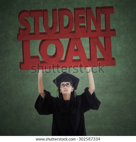Portrait of female bachelor wearing graduation gown and holds student loan text