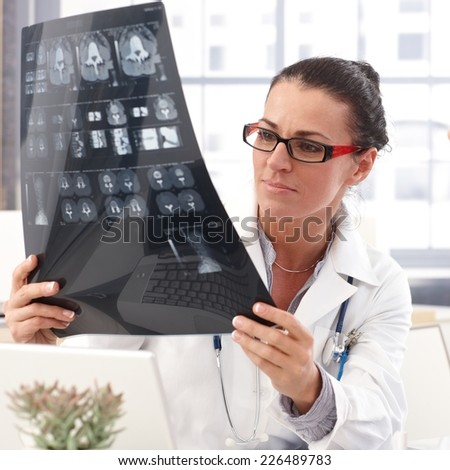 Portrait of female brunette doctor with x-ray image in hand, wearing glasses, stethoscope and lab coat,