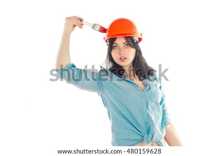 portrait of female builder with brush in hand looking at the camera isolated on white background