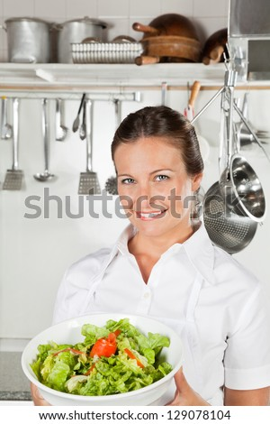 Portrait of female chef holding bowl of salad in restaurant kitchen - stock photo