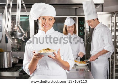 Portrait of female chef presenting dish with colleagues working in industrial kitchen