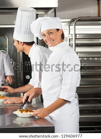 Portrait of female chef with tong and dish in restaurant kitchen