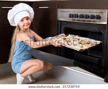 Portrait of female child baking Italian pizza at home  - stock photo