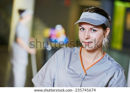 portrait of female cleaner in front of cleaning worker with mop and cleaning equipment - stock photo