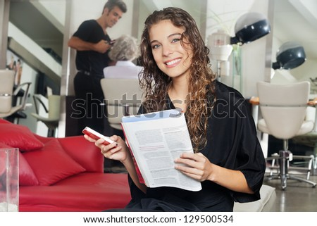 Portrait of female client holding mobile phone and magazine with hairdresser working in the background at hair salon - stock photo
