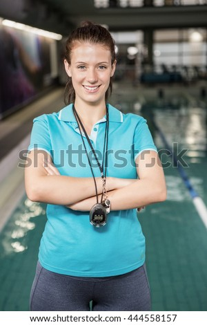 Portrait of female coach standing with arms crossed at leisure center