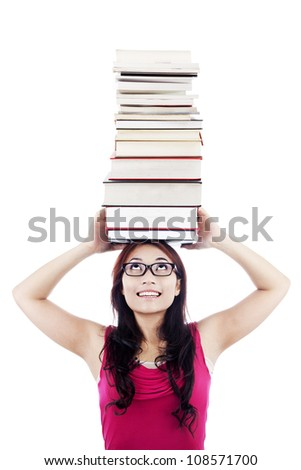 Portrait of female college student carrying a pile of books over her head - stock photo