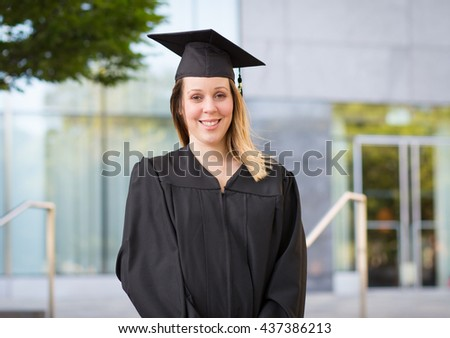 Portrait of female college student in graduation cap and gown on campus