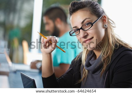 portrait of female college student sitting in library with laptop computer and looking at camera. Horizontal shape, side view, copy space