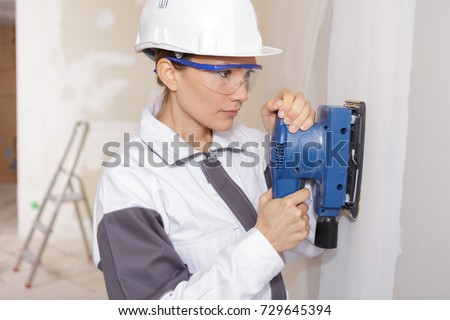 portrait of female contractor using sander on plasterboard wall