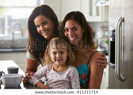 Portrait of female couple in the kitchen with their daughter - stock photo