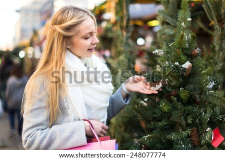 Portrait of female customer choosing Christam tree outdoor - stock photo