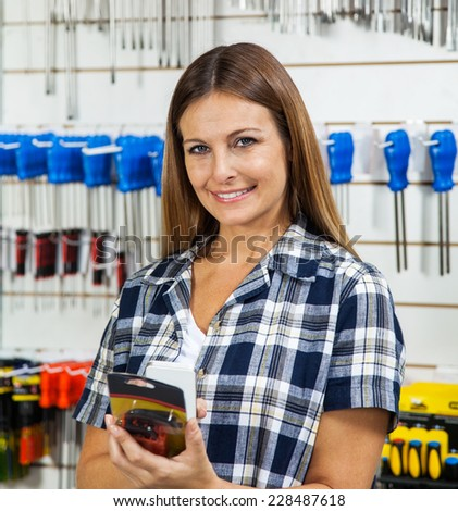 Portrait of female customer scanning product's barcode through cellphone in hardware store - stock photo