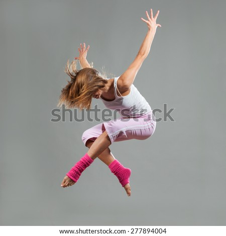 Portrait of female dancer performing in mid air. Jumping pose concept. - stock photo