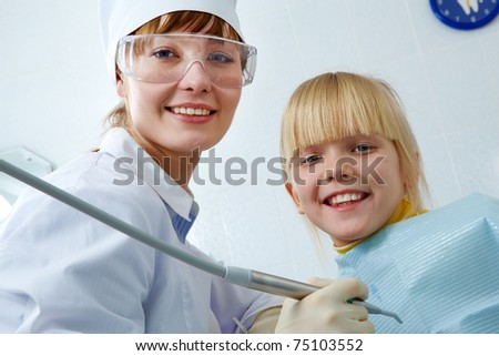 Portrait of female dentist and little girl looking at camera - stock photo