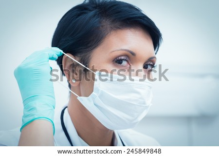 Portrait of female dentist wearing surgical mask - stock photo