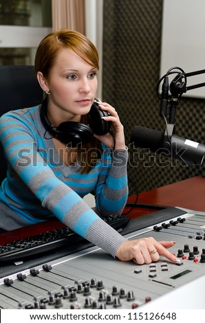 Portrait of female dj working in front of a microphone on the radio - stock photo